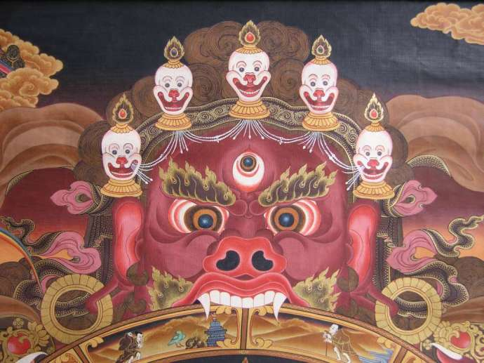 This is a painting of Yama, the Lord of Death, who holds the wheel in his mouth and embraces it with his claws. It symbolises the inevitability of death, samsara and the impermanence of all things. Yama has a horrific face with projecting fangs and a forehead wreathed in the macabre five-skull crown.